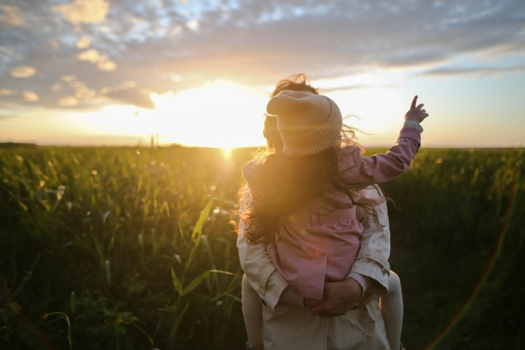 This is an image of a child pointing at a sunset over a cornfield, from piggy-back on her mother.