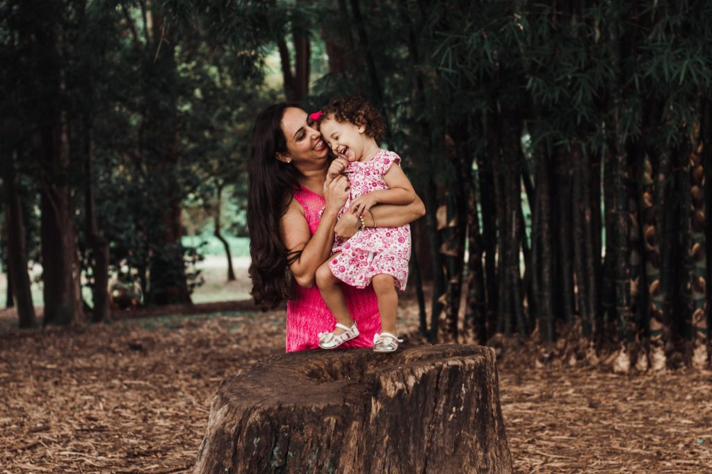 A mother holding a toddler on a stump to kiss the child.