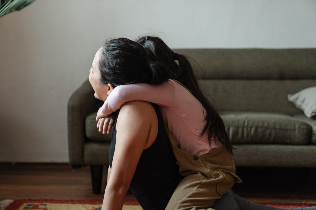This is an image of a child draped happily over the back of her seated and laughing mother.