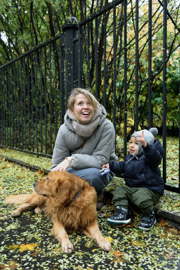 This is an image of a mother sitting outdoors with a child and a golden retriever dog.
