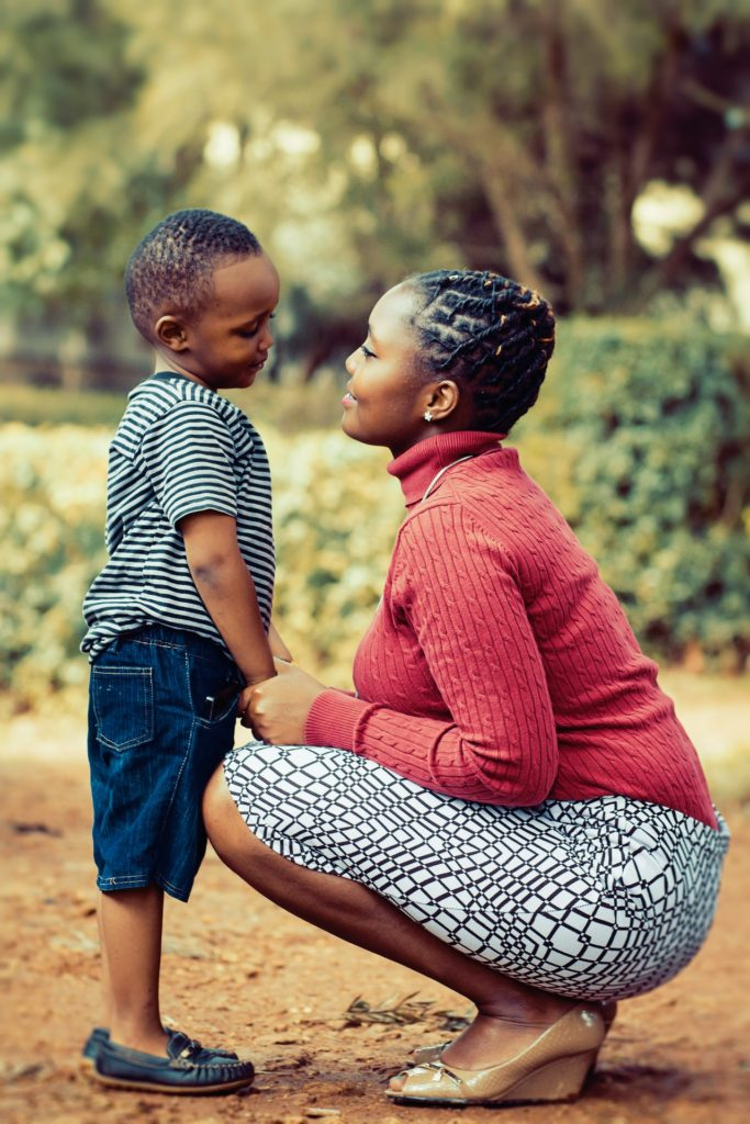 A mother kneels down to her child's level and smiles into his face.